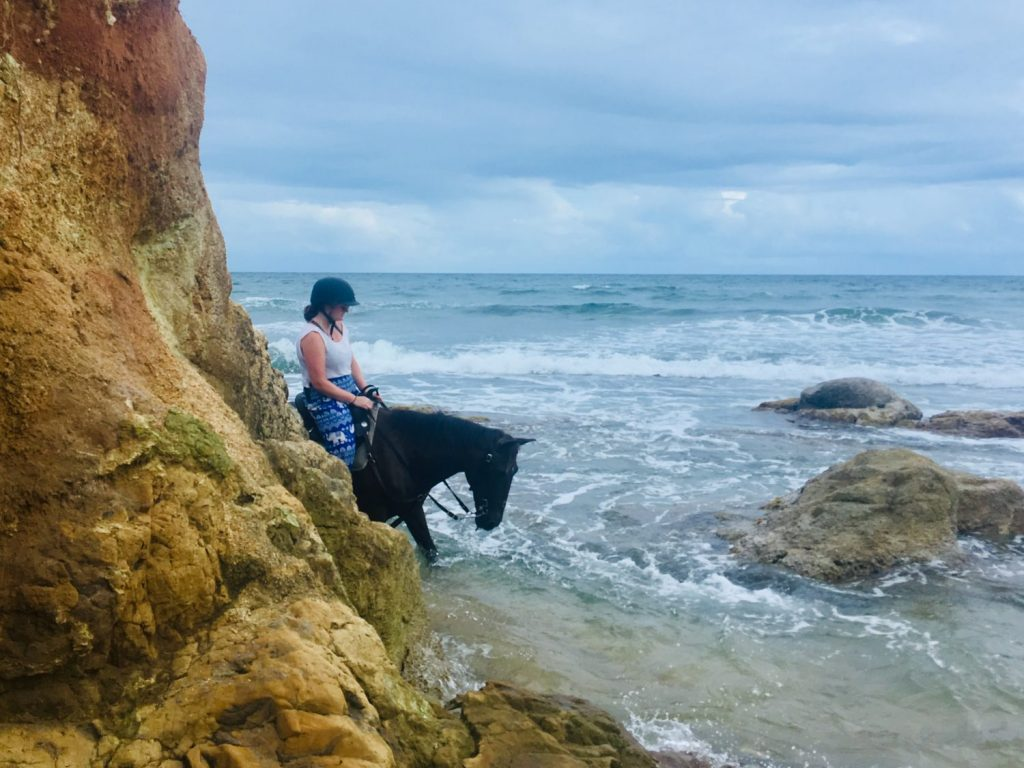 Woman riding horseback in the ocean on an exotic beach vacation