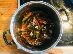 Pot of simmering green lip mussels on top of a stove